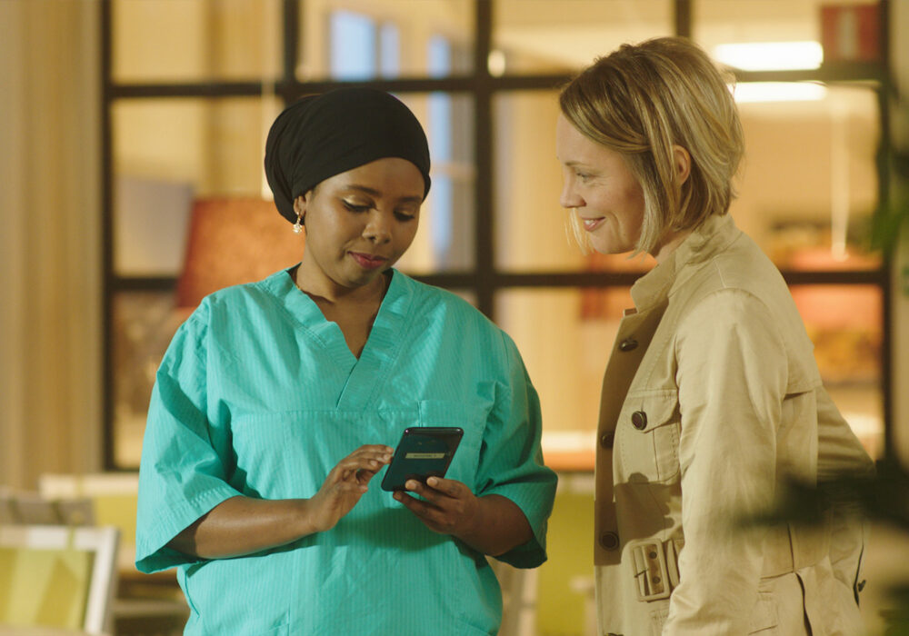 Woman smiles as she is looking at a carer using Nectarine Health mobile app