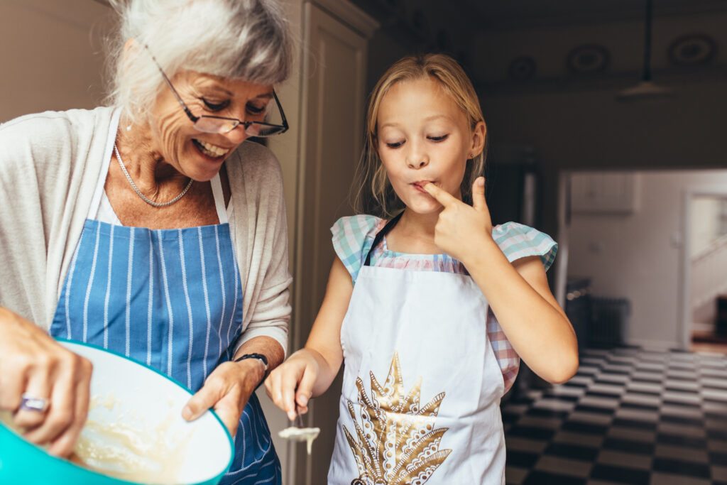 Grandmother and a young girl having fun baking a cake in the kitchen