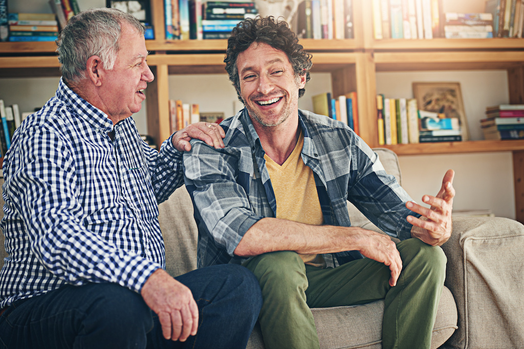 A mature man and his elderly father sitting on the sofa at home and having a chat